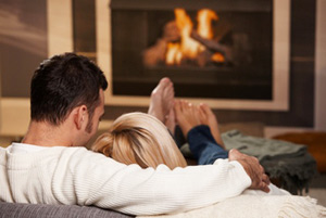 Couple snuggled up by log fire